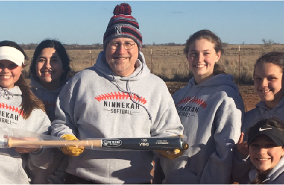 Shoemake Holds Tribute Bat Received For Coaching 100th Softball Win